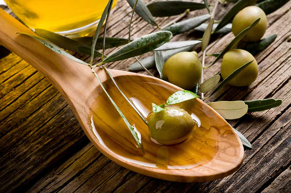 Extra virgin olive oil and olives in wooden spoon